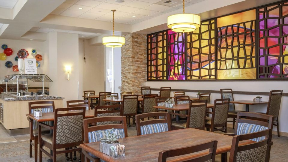 "Five Tableaux ""Elements"" decorative grilles make up this double sided art wall in the GenCare Lifestyle Point Ruston dining room."